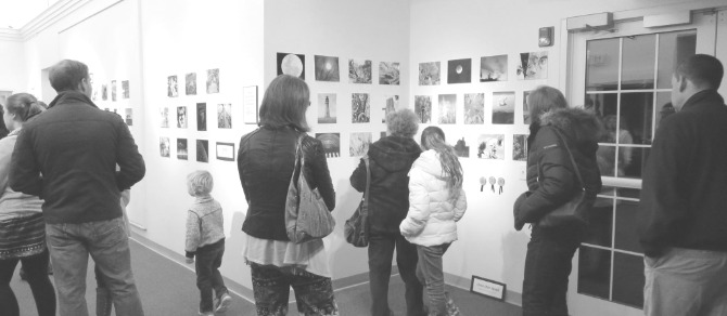 Adults and children making their way through one of our past photography contest openings.